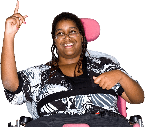 A woman in a wheelchair, smiling and raising her hand to say something