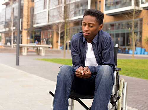 A young man in a wheelchair looking stressed