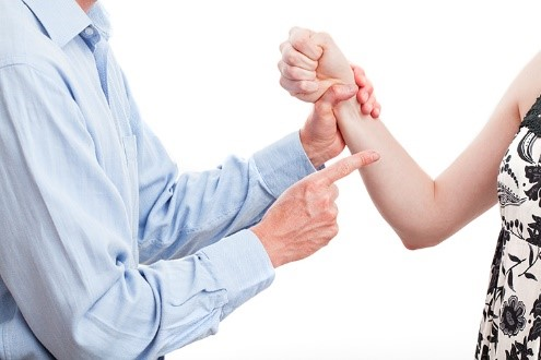 A man grabbing a woman by the wrist and pointing at her with his other hand. The woman is trying to get away.